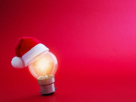 Light bulb and Santa Claus hat over red background with copy space. Christmas and New year holidays concept.