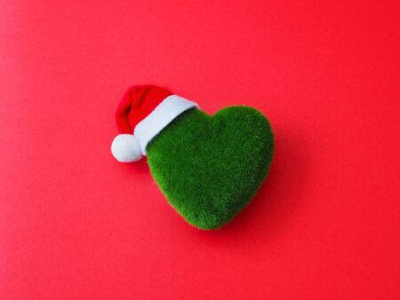Close up green heart shape and Santa Claus hat on red background.