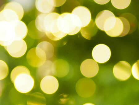 Abstract gold and white bokeh on green color for Christmas background.