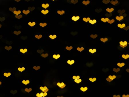 Golden blurred bokeh heart shape abstract background on black color. Zdjęcie Seryjne