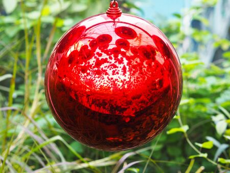 Close up hanging red ball Christmas ornament with reflection for decoration party.