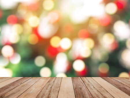 Wooden table top over bokeh of colorful light on Christmas pine tree background. Montage style to display the product. Zdjęcie Seryjne