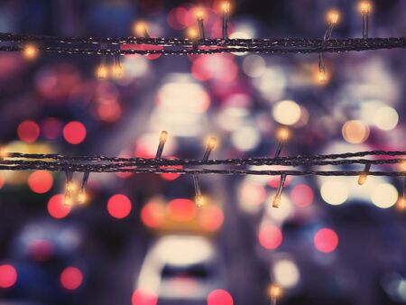 Close up LED lighting and wire decoration over blur background of traffic light on street. Christmas and new year background.