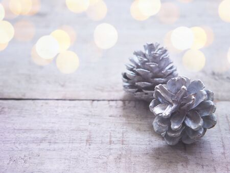Close up white pine cone on vintage wood with golden bokeh. Christmas and winter holiday background.