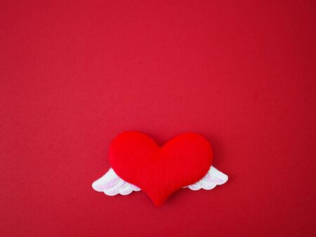 Close up soft red heart shape with two shiny white wings on red paper. Love concept for Valentine day background.