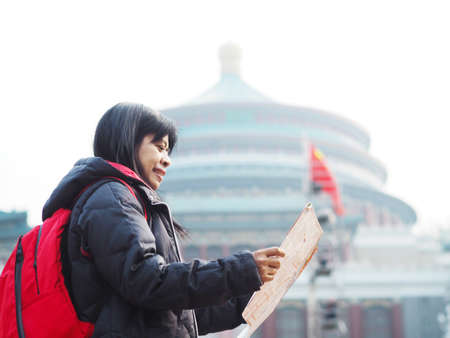 Asian smiling woman looking at the map over blur background of Great Hall of Chongqing people's Square or Chongqing People's Auditorium, landmarks in Chongqing at China.