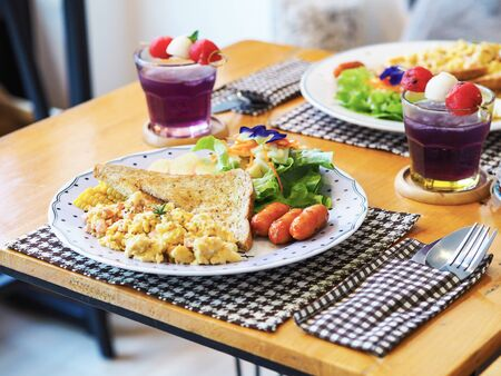 American breakfast set on wooden table in the morning. Close up toasted bread with fruit juice on white plate. Archivio Fotografico - 142810661