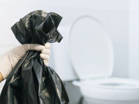 Close up hand with glove holding black garbage bag over blurry white toilet background. Cleaning home concept.