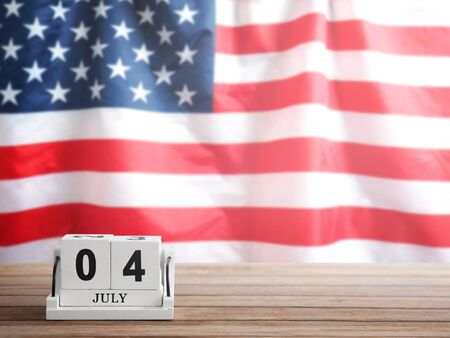White vintage wood block calendar present date 04th of July on brown wooden table over USA flag blur background with copy space. Happy flag day