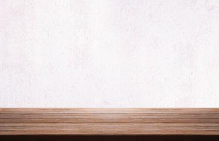 Holztischplatte über weißem Grunge Vintage Betonmauer verschwommenen Hintergrund.