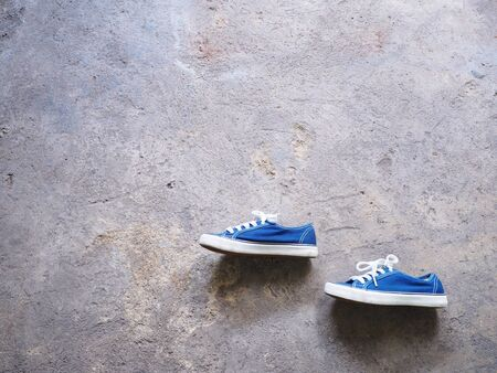 Side view of pair blue sneaker shoes on grunge concrete background.