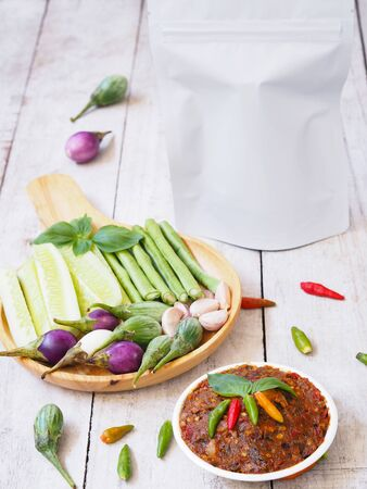 Spicy fermented fish chili paste dipping and white blank zipper bag packgaging with fresh tropical vegetables on white vintage wooden table.