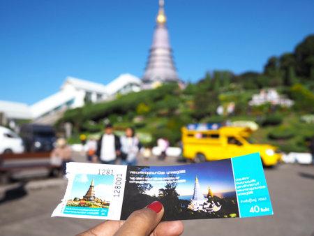 Chiangmai, Thailand - 14 January 2019 : Woman hand hold the entrance ticket to Phra Maha Dhatu Nabhamethanidol and Nabhapolbhumisiri (The Great Holy Relics Pagoda Nabhamethanidol and Nabhapolbhumisiri) at Chiangmai province, Thailand. Editorial