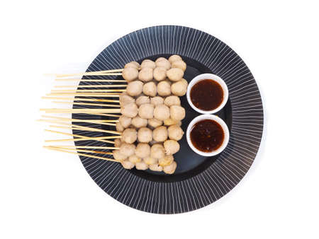 Top view of grilled meat ball with cups of sweet spicy sauce on black plate isolated on white background. Foto de archivo