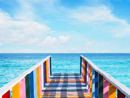 Colorful rainbow vintage wooden bridge on the sea over blue sky background at pier.