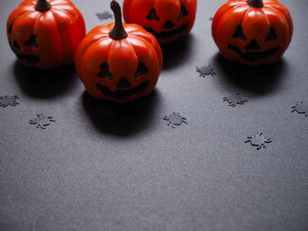 Top view of orange pumpkin, white spiders and yellow web shape on black grunge texture for halloween background concept.