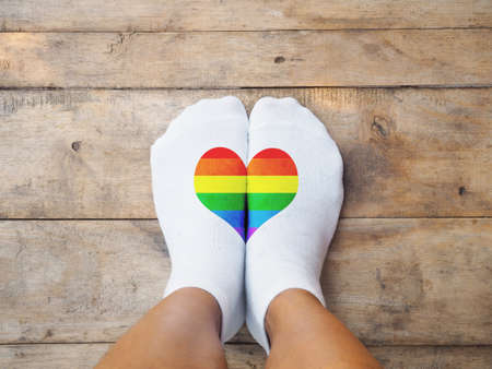 Selfie feet wearing white socks with rainbow color heart shape on wooden floor background. LBGT love concept.