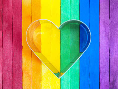 Heart shape frame on colorful wooden background. LGBT day concept.