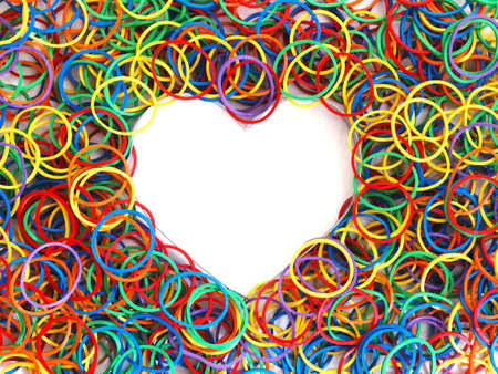 Close up heap colorful rubber bands in heart shape on white backgroud. Love and LGBT pride concept.