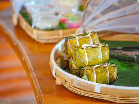 Close up heap of steamed sticky rice with banana inside ( Kao tom mud) wrapped by banana leaf on bamboo tray. Traditional Thai homemade dessert.