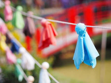 Close up Japanese fabric rain doll or Teru teru bouzu hanging in row at Japan garden.