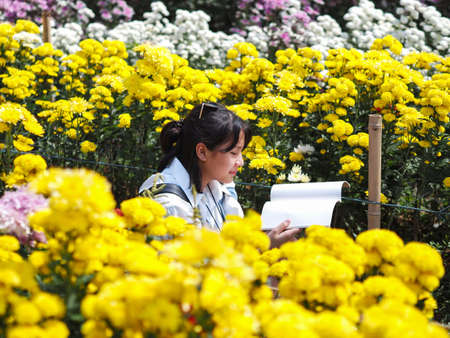 Asian happy girl sitting in the colorful flowers garden and reading the book.