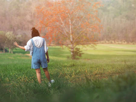 Asian pretty girl wearing casual cloth walking and dancing through a green field, summer outdoor.