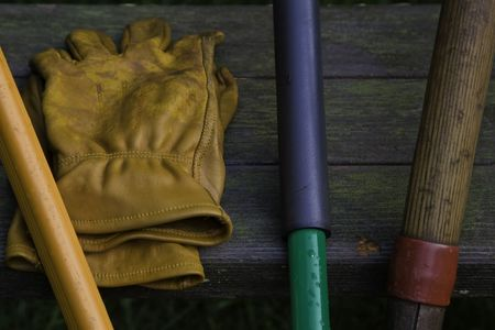 groundskeeper: Yellow leather garden gloves and tool handles. Stock Photo