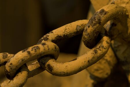 Close-up of chain on an old backhoe, shot at dusk, lit by streetlight. Stock Photo