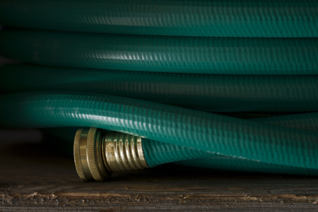 frontyard: Green garden hose with brass fitting coiled on an old wooden plank. Stock Photo