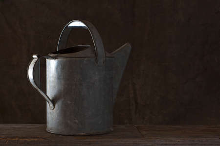 frontyard: Still life of rustic old watering can on an old wooden plank. Stock Photo