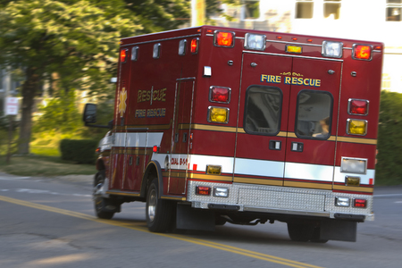emt: Red emergency rescue vehicleambulance rushing to scene of an emergency.