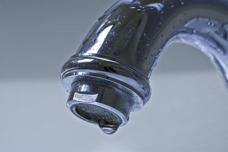 Water dripping from a silver, chrome bathroom faucet. photo