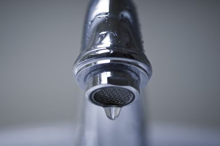 Water dripping from a silver, chrome bathroom faucet. Stock Photo