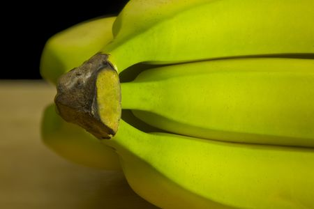 unripened: Bunch of green bananas against a black background.