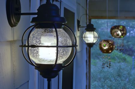 Pair of exterior compact fluorescent electric light fixtures on screened porch. Stock Photo - 3033216