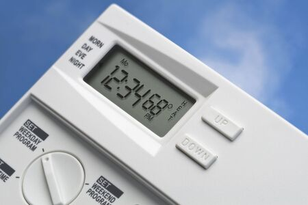 global cooling: Programmable digital thermostat against a blue sky and cloud background.