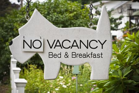 booked: Sign in front of New England Bed and Breakfast with flap for no vacancy.