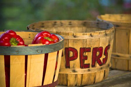 Red peppers in hand-letterd bushel basket at a roadside market photographed at sunset.