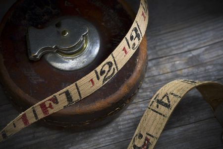 bygone: Antique tape measure with a brown leather case on an old wooden workbench.