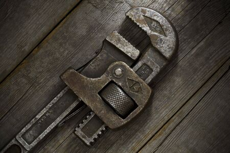 Trusty, old wrench on an old wooden workshop bench. 版權商用圖片