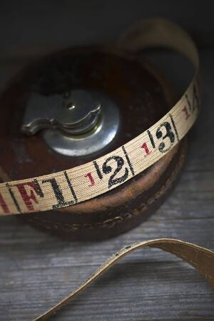 Antique tape measure with a brown leather case on an old wooden workbench.