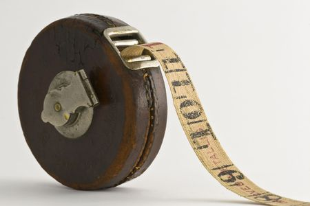 Antique tape measure with a brown leather case on a xxx background. Фото со стока