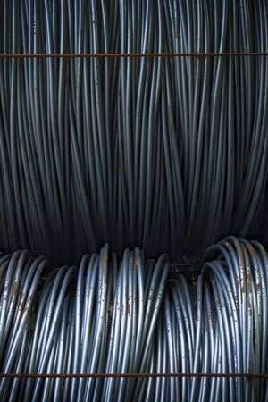 steel cable: Wire coils, some rusted, in a factory lot.