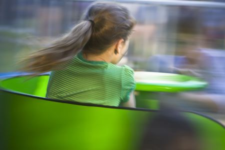 captured: Pony-tailed girl on a bright green twirling carnival ride. Motion blur was captured in-camera with slow exposure and is intentional.
