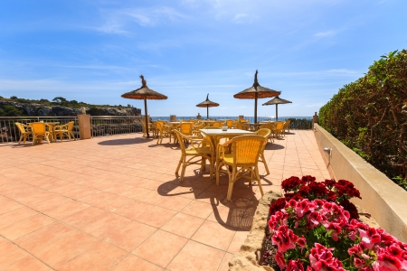 Red flowers and tiled floor of restaurant sunny terrace in Cala Figuera town, Majorca island, Spain