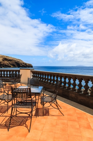 Sea view and metal chairs with glass table on restaurant terrace on sunny summer day , Madeira island, Portugal photo