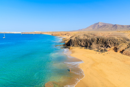 Couple of people in turquoise ocean water on Papagayo beach, Lanzarote, Canary Islands, Spain Reklamní fotografie - 48652303