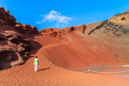 golfo: Young woman tourist walking on red lava hills near Lago Verde lake, El Golfo, Lanzarote, Canary Islands, Spain