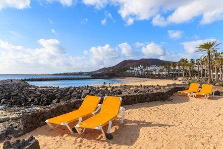 playa blanca: Sunbeds on Playa Blanca volcanic beach, Lanzarote, Canary Islands, Spain Stock Photo